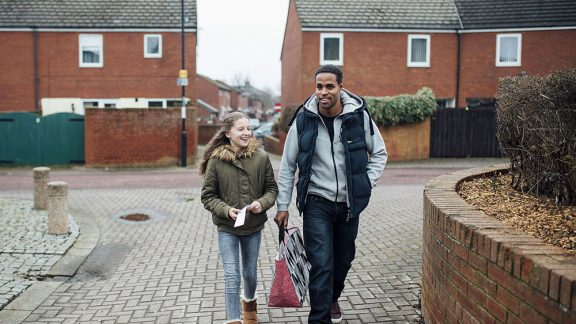 a man and girl walking on the street smiling