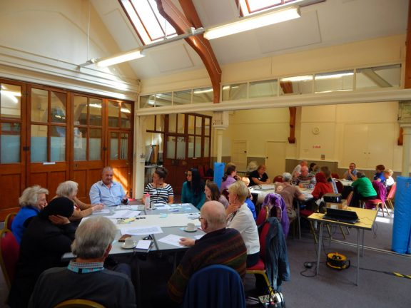 people gathered round tables in a village hall