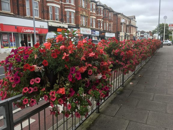 flower baskets on a railing in Southport